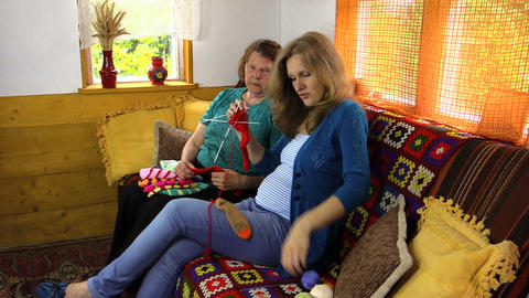 amiable grandma teach pregnant granddaughter to knit baby socks Footage