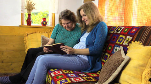 zoom out pregnant woman granny read book, generations leisure Footage