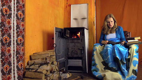 young girl found interesting book and read near to the stove Live Action