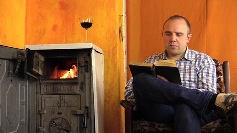man read book sip wine next to ancient smoldering fire stove Footage