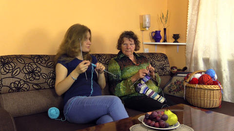 grandma with girl knit needles on couch, experience, hobby craft Footage
