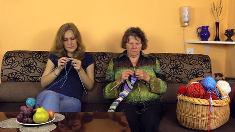 Old grandmother knit with nurse woman on sofa in nursing home Footage