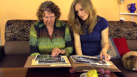 Happy granddaughter woman with senior grandmother look at photos Footage