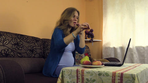 pregnant woman work at home with laptop, snack grape, fruit vase Footage