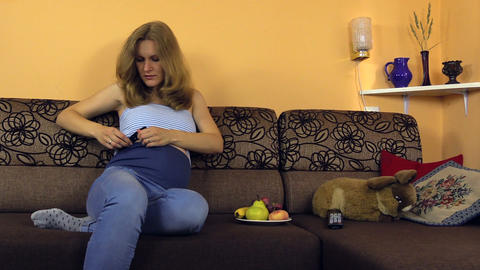 Pregnant woman lie on couch and fix her pants stomach protection Footage