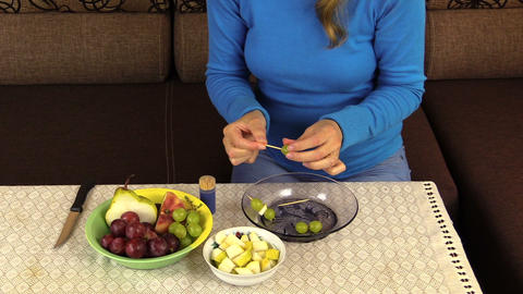 hand string grape pear fruit on stick and put pan on table Footage