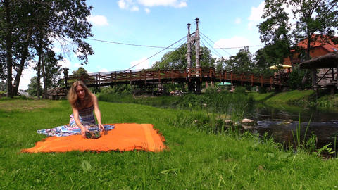 Woman prepare picnic place on orange plaid rug near river water Footage