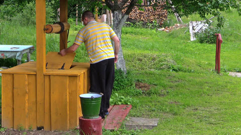 young man turning old rural yellow well handle in countryside Footage