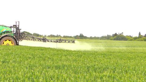tractor spray liquid fertilizer on crop field. agricultural work Footage