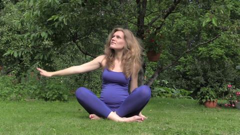 Healthy pregnant woman do yoga exercise sit on grass in nature Footage
