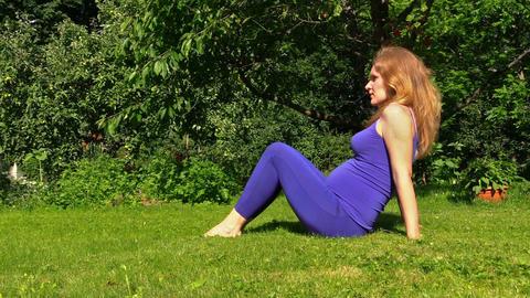 pregnant woman make exercise for leg in garden. Prenatal health Footage