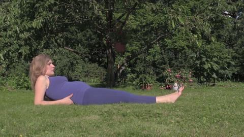 pregnant girl make exercise leg lie on grass. Prenatal sport Footage