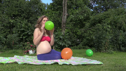 Cute pregnant woman girl inflate colorful balloon in garden Footage