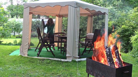 smoldering wood on grill. Woman rest in gazebo in green park Footage