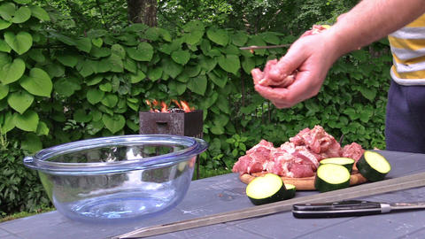 hands stab meat and vegetable pieces on skewer. Fire in barbecue Footage