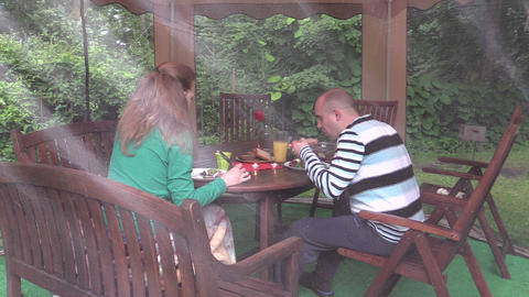 couple eat backed meat at table with candle in garden gazebo Footage