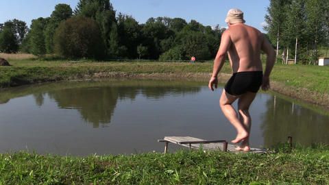 Middle-aged man make head jump into pond water from bridge Footage