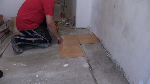 Bucket full of adhesive glue and handyman man measure tiles Footage