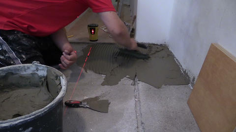 man distribute mass tile glue on floor. Laser level measure Footage