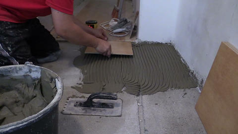 Master man lay ceramic floor tiles in kitchen Footage