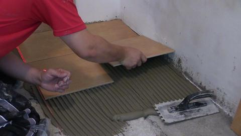 man hand bond ceramic floor tile at home. Home renovation Footage