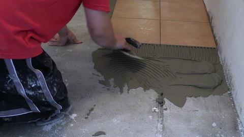 Lay ceramic floor tiles - man spread adhesive material. Closeup Footage