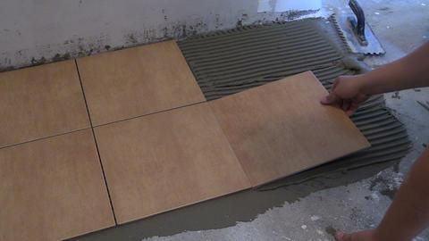 worker glue ceramic tile on floor at home. Home renovation Footage