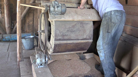 Farmer man turn handle of sifting equipment tool and sift grain Footage