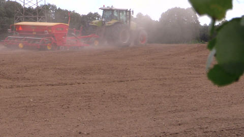 Tractor spread fertilizer on cultivated field. Tree leaves move Footage