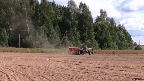 Tractor spread fertilizer on cultivated field near forest Footage