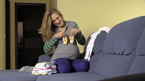 Happy pregnant future mom prepare newborn clothes and shoes Footage