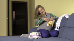 Happy pregnant future mother prepare newborn clothes and shoes Footage