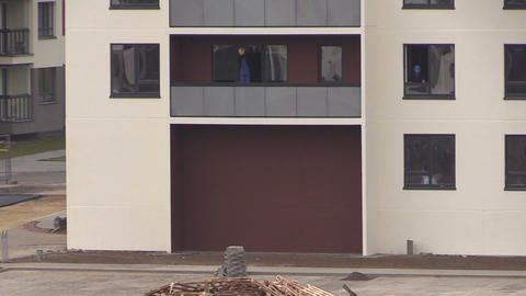 workers with helmets clean window in new build residential house Footage