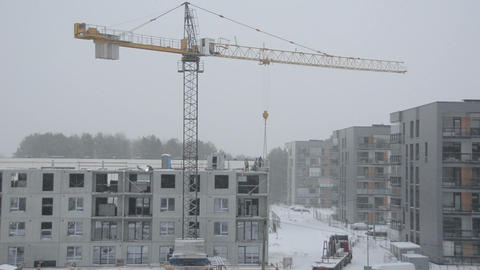 Dramatic snow fall and construction site workers builders work Footage