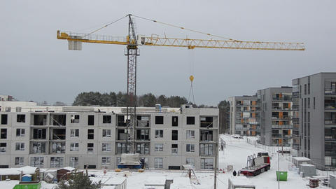 Winter construction site with cranes and workers building house Footage