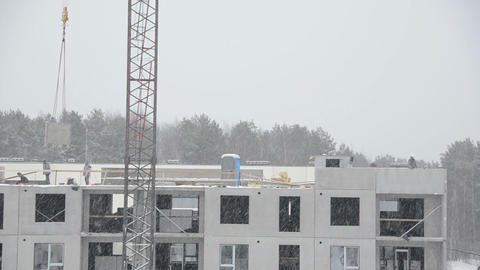 Winter snow fall and workers with crane lift block house parts Footage