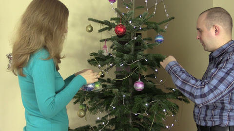 Married couple decorate fir tree with ball toys on Christmas eve Footage