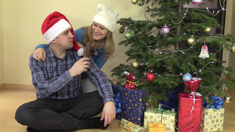 Happy couple with hat eat delicious Santa shape chocolate Footage