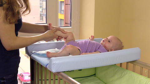 Mother massage and exercise her little baby daughter legs on bed Footage