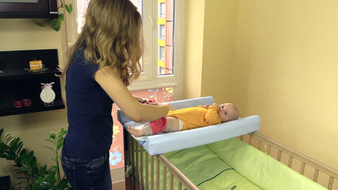 mother dressing baby with pink pants. Kid lie on changing table Footage