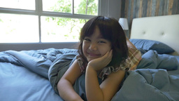 Slow motion of cute little Asian girl laying on the bed Footage