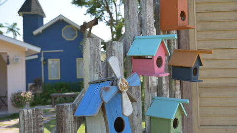 Colorful Wooden Bird House On The Fence, Tilt Down Shot stock footage