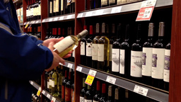 A hand takes bottles of wine from the shelf Footage