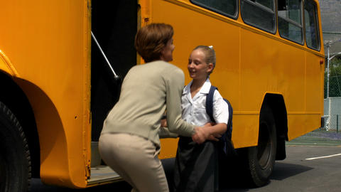 Mother dropping her little girl to school bus Live Action