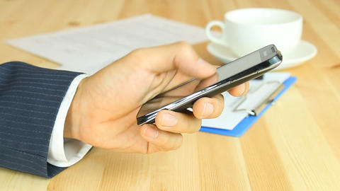 Businessman Sliding Smart Phone By One Hand on Working Table Footage
