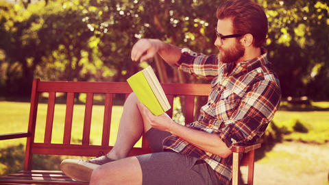In high quality 4k format handsome hipster reading in the park Footage