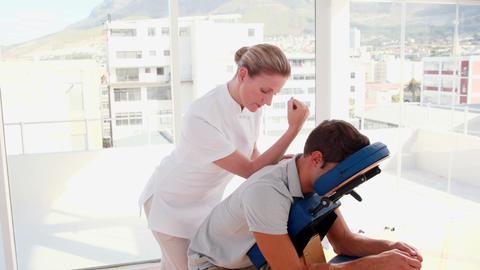 Female therapist massaging man sitting on massage chair Footage