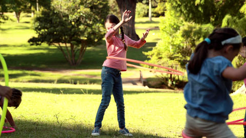 Little friends playing with hula hoops in park Footage