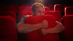 Young man watching a scary film Footage