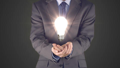 Businessman presenting light bulb with hands Footage